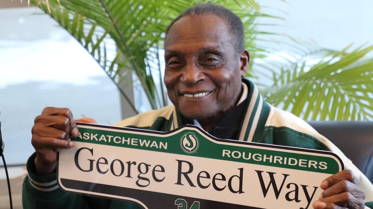George Reed tient une plaque de rue qui porte son nom.