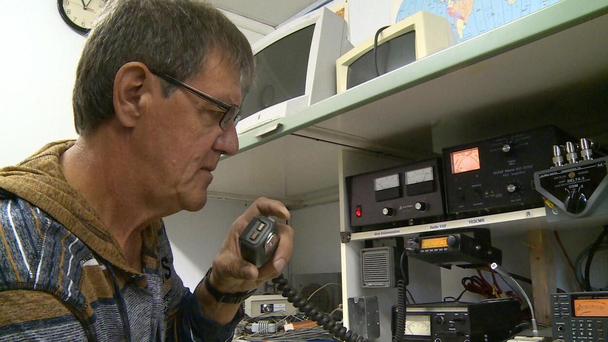 Un homme qui parle dans un microphone relié par un fil à des installations de radio amateur.