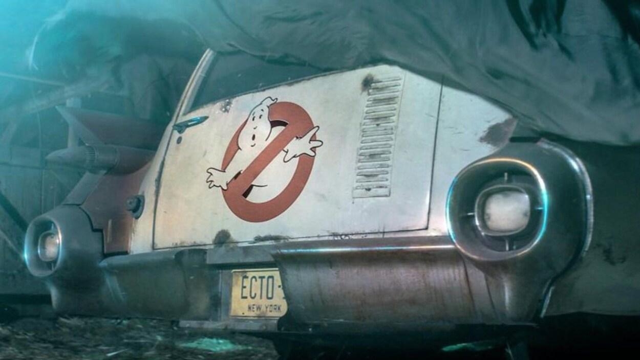 Photo de l'arrière d'une voiture blanche sur laquelle se trouve le logo des Ghostbusters.