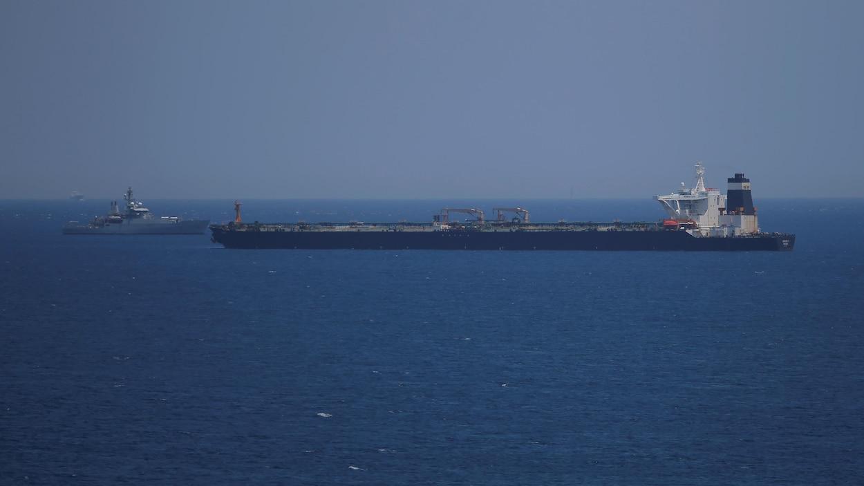 Un pétrolier et une frégate se font face au large d'une mer.