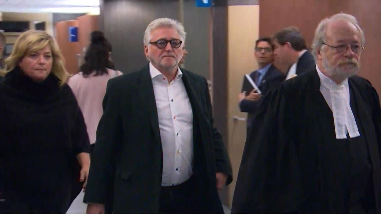 M. Rozon porte des lunettes, un veston et une chemise. Devancé par son avocat, il regarde la caméra, impassible.