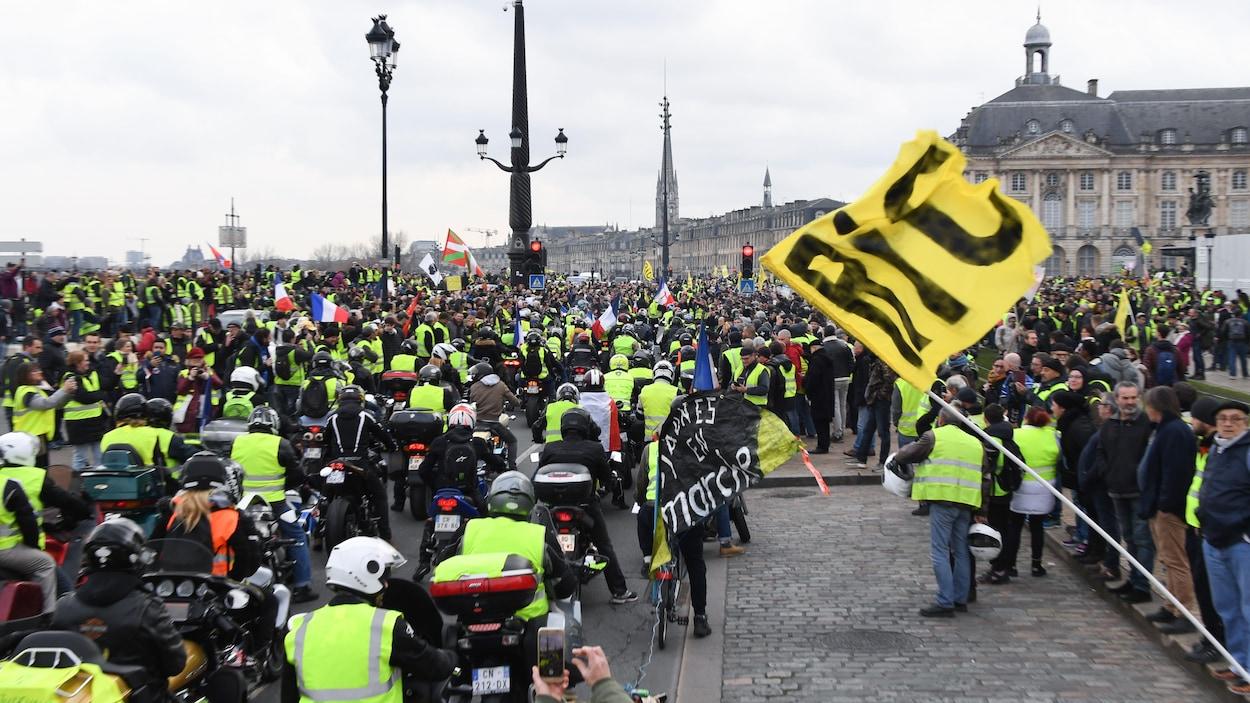 Des motocyclistes et des manifestants à pied sont réunis.