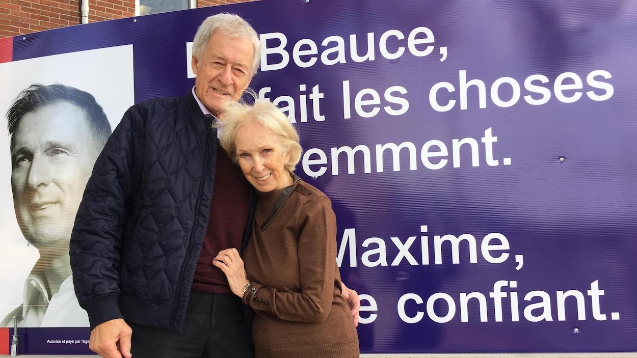 Gilles Bernier et Doris Rodrigue-Bernier posent devant une affiche électorale de Maxime Bernier.