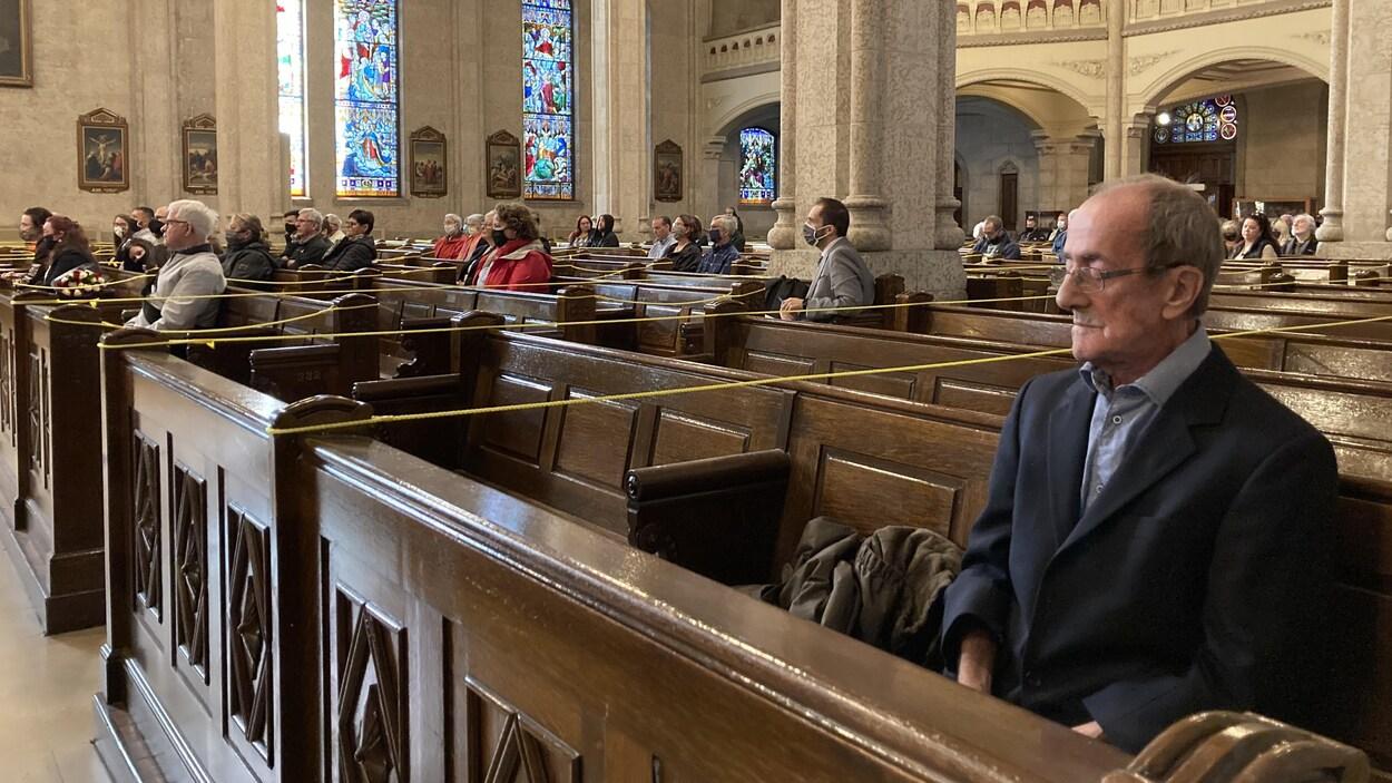 Gilles Kègle assis sur un banc d'église.