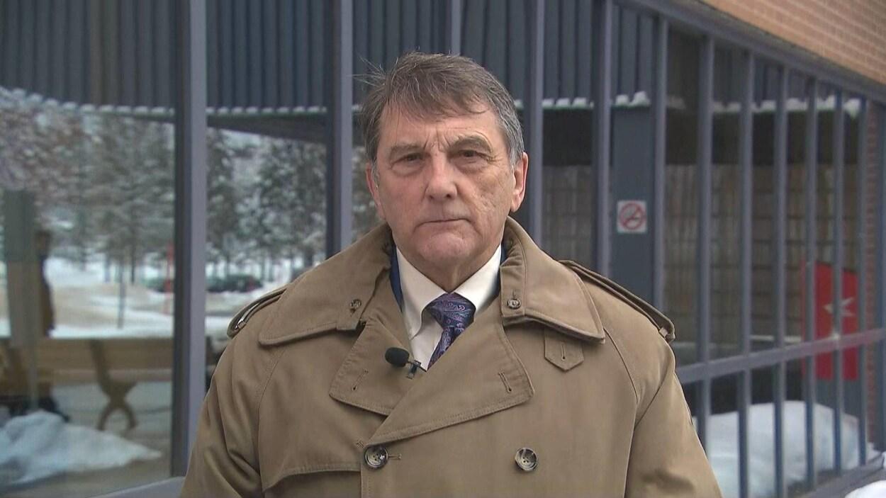 Gilles Lanteigne à l'extérieur, vêtu d'un manteau d'hiver, devant un édifice.