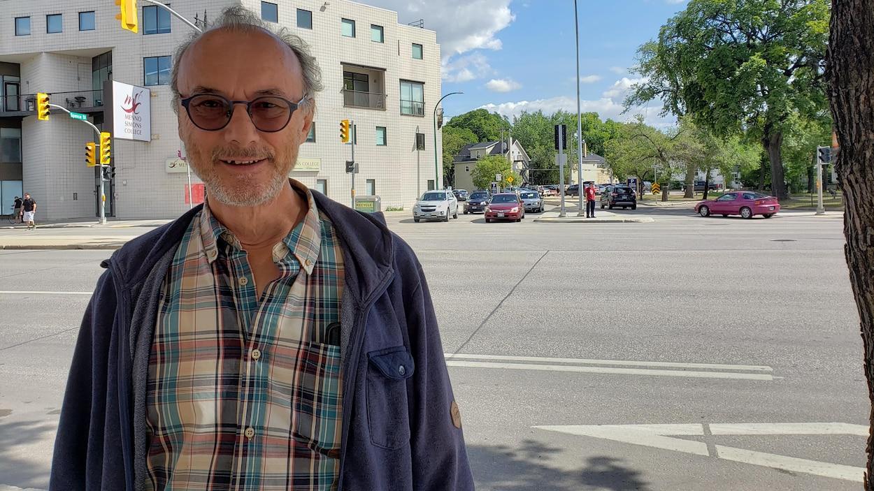 Gilles Lesage sourit pour une photo. Il est à l'extérieur, devant une rue de Winnipeg.