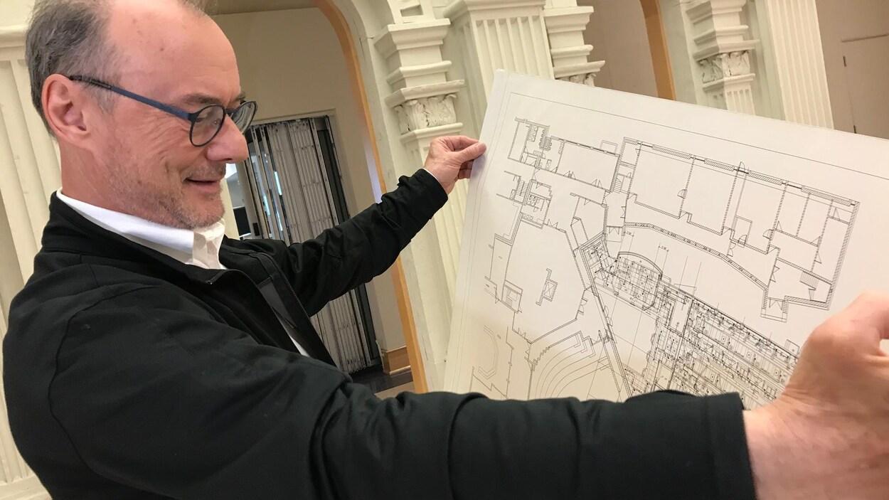 Le directeur du Centre du patrimoine tenant les plans de construction du centre.