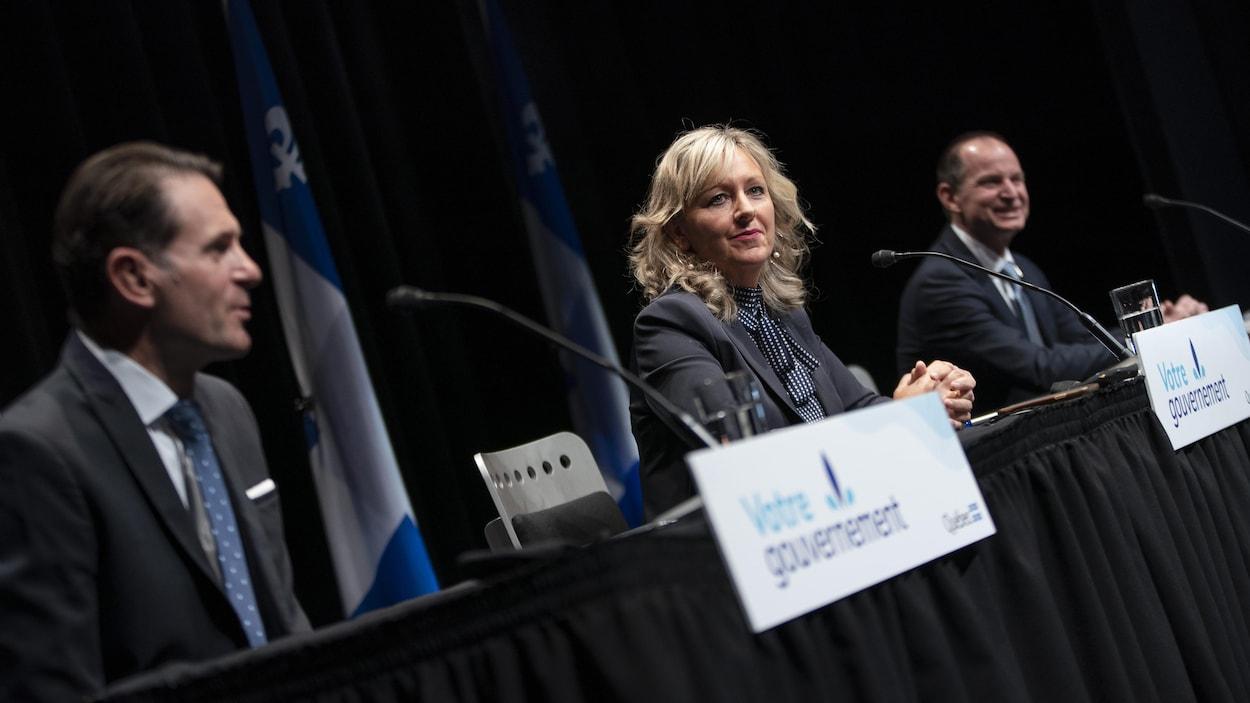Trois personnes assises durant une conférence de presse.