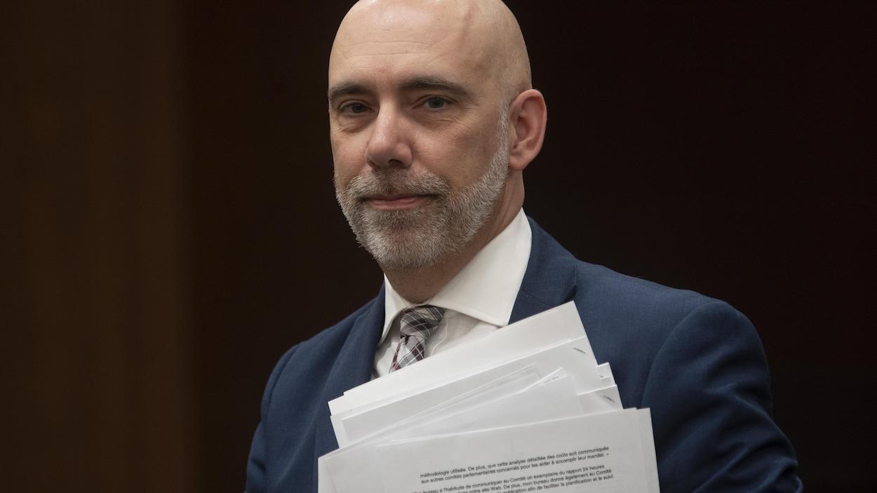 Le directeur parlementaire du budget, Yves Giroux, tient des documents.