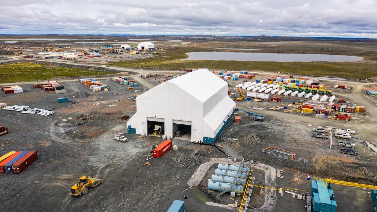 Vue de haut d'un complexe minier avec des conteneurs, des camions et un lac.