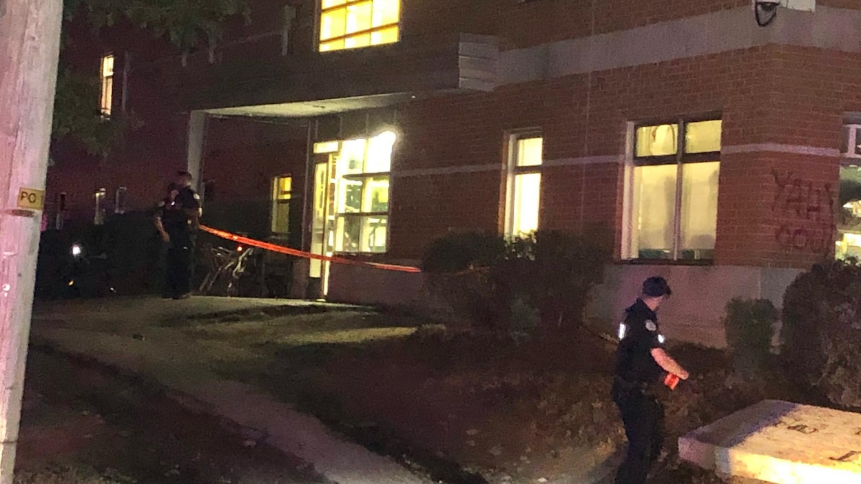 Deux policiers déploient un cordon de sécurité devant un immeuble de Gatineau, la nuit.