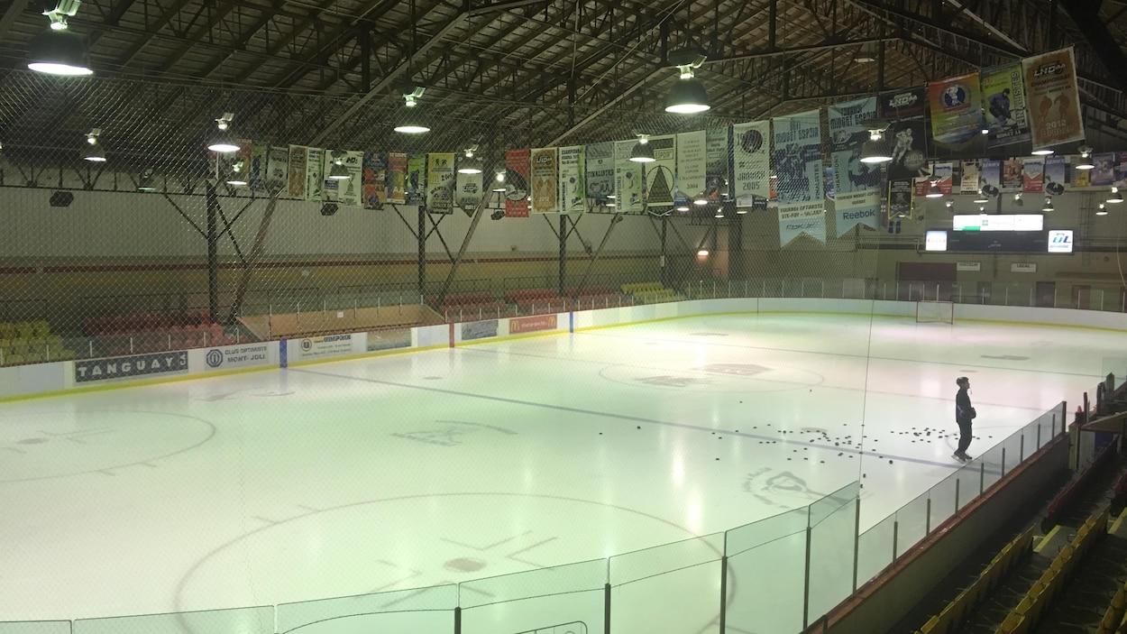 Vue de la glace de l'aréna du Stade du centenaire à Mont-Joli. Un patineur est sur la glace, entouré de dizaines de rondelles.