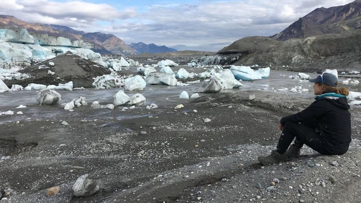 Une habitante de Whitehorse, Haley Digel, assise par terre observe le 15 juillet un grand espace se trouvait un lac du glacier Donjek.