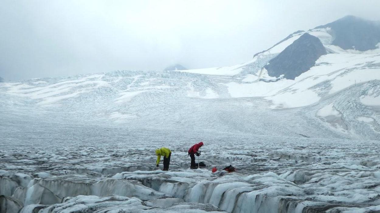 Deux personnes étudient le sol dans une étendue glacée, dans le Nord canadien.