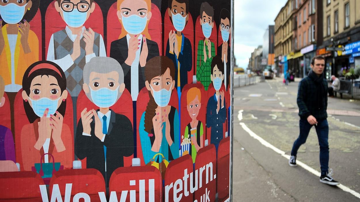 Un homme marche dans la rue sans masque. Sur une affiche, on voit une dizaine de personnes portant le masque.