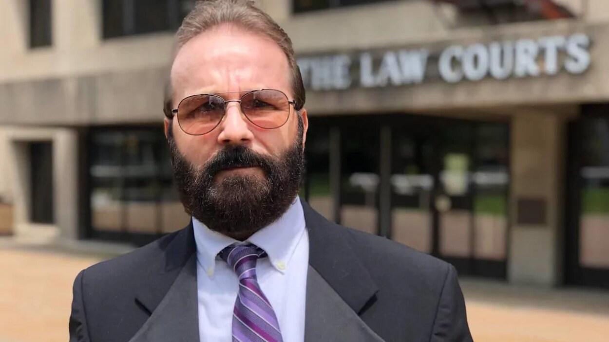 Glen Assoun portant un complet, une cravate et des verres fumés devant la Cour suprême de la Nouvelle-Écosse.