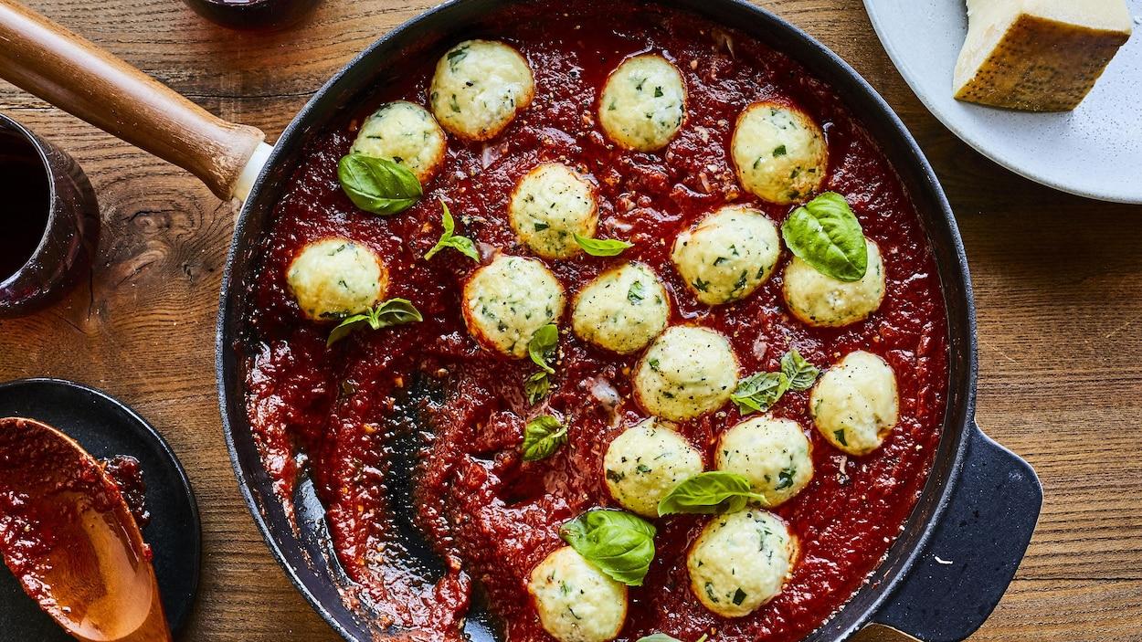 Une poêle remplie de gnudis, de sauce tomate et de basilic repose sur une table à manger, aux côtés d'une spatule tachée de sauce et d'une assiette avec du parmesan.