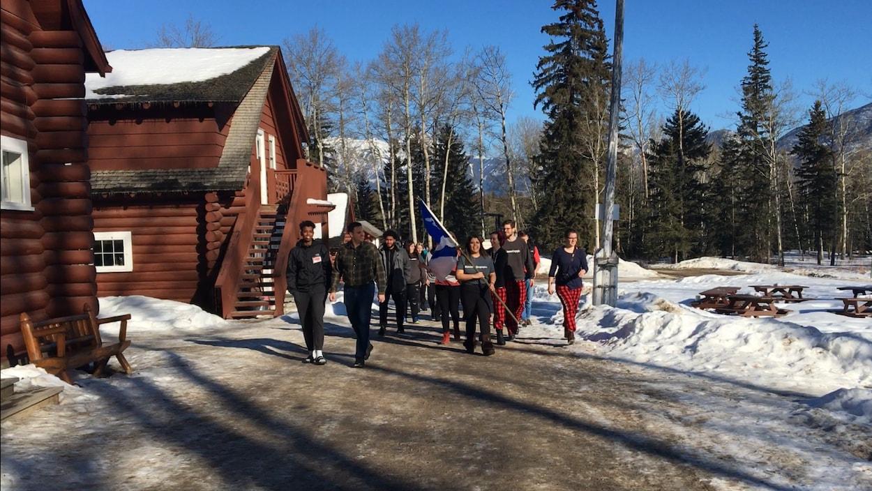 Devant les montagnes de Jasper, un groupe de jeunes avancent avec un drapeau franco-albertain.