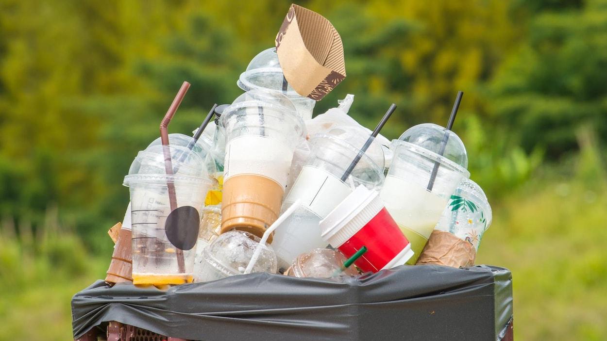 Une poubelle est pleine de gobelets et de pailles en plastique.