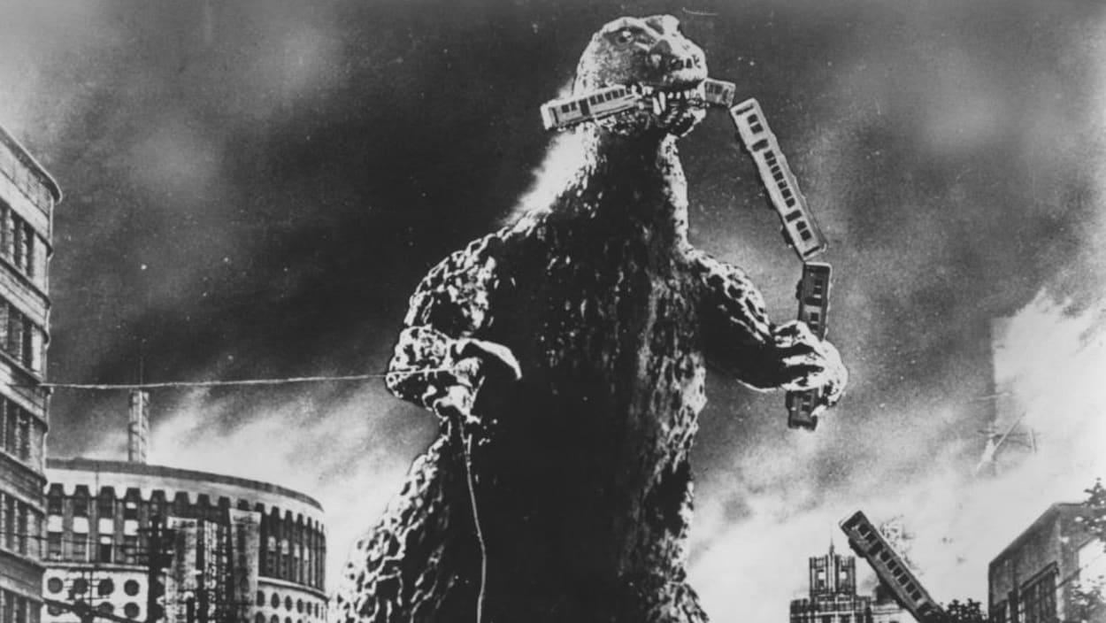 On voit le monstre « Gojira » en train de dévorer un train, dans une ville.