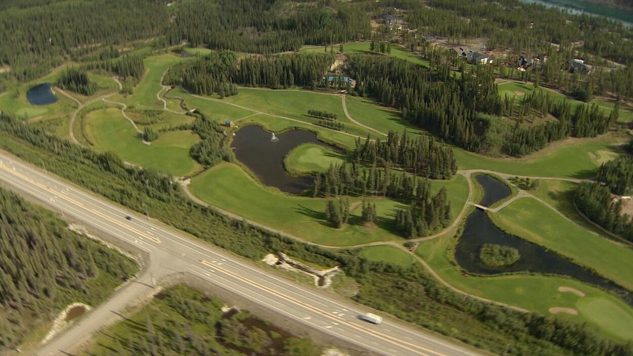 Une vue aérienne d'une route et du terrain de golf Meadow Lakes à Whitehorse
