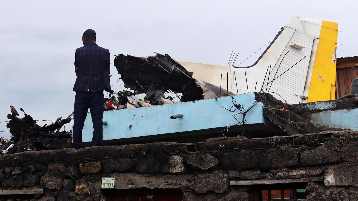 Un homme debout sur le toit endommagé d'une maison à côté de la queue d'un avion.