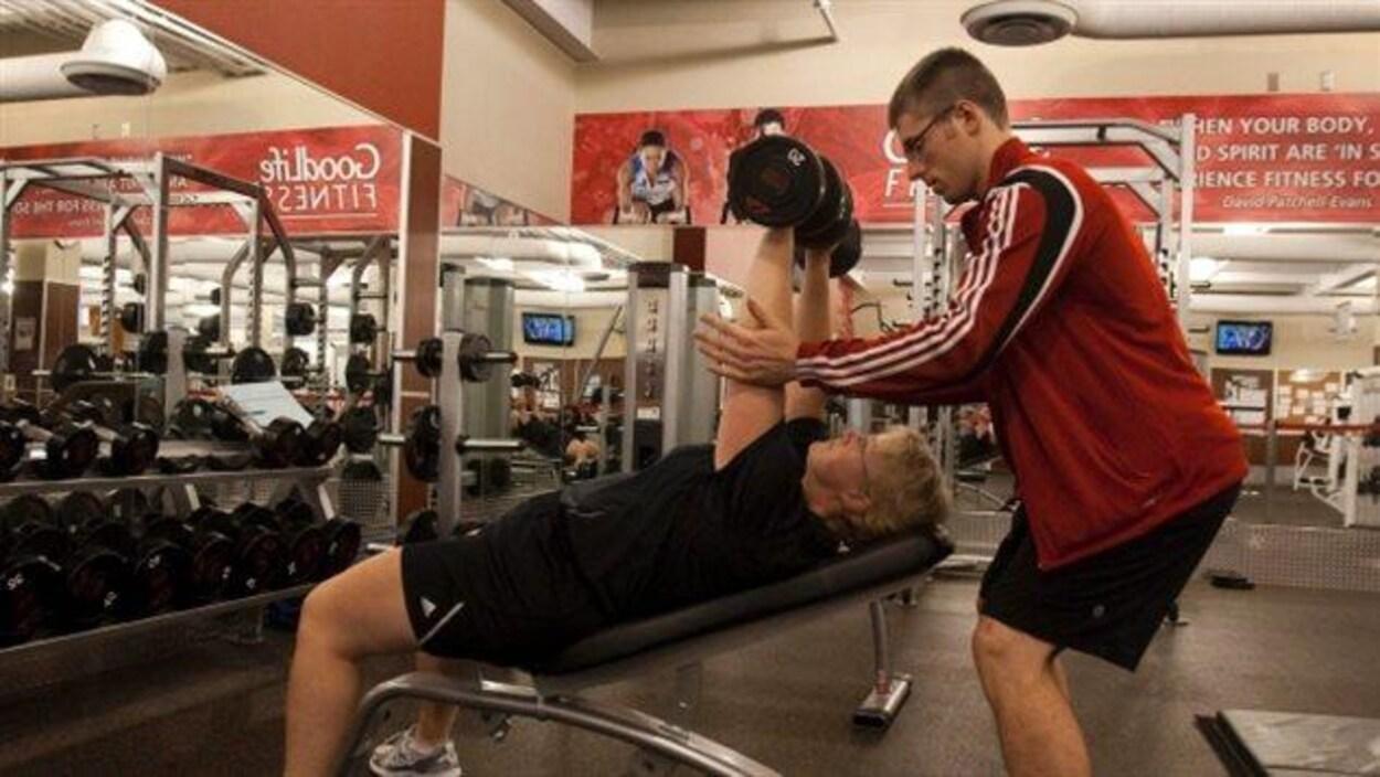 Un entraîneur de GoodLife Fitness aide une cliente