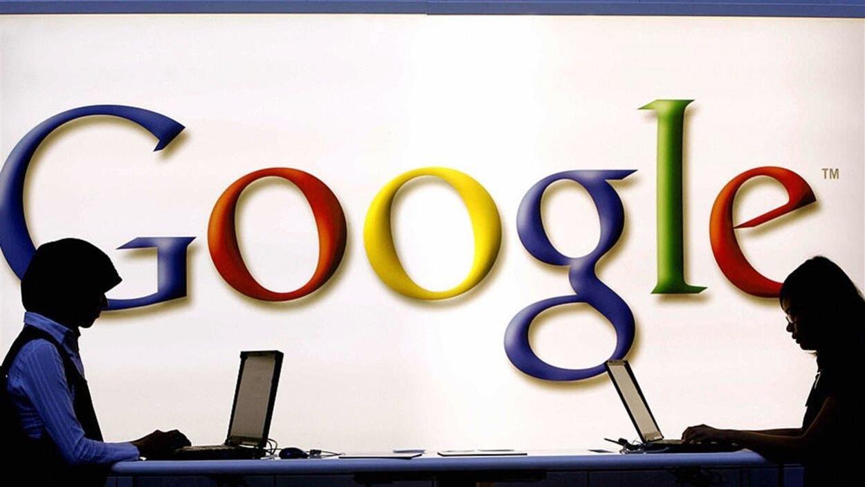 Deux personnes travaillent sur des ordinateurs devant le logo de Google.