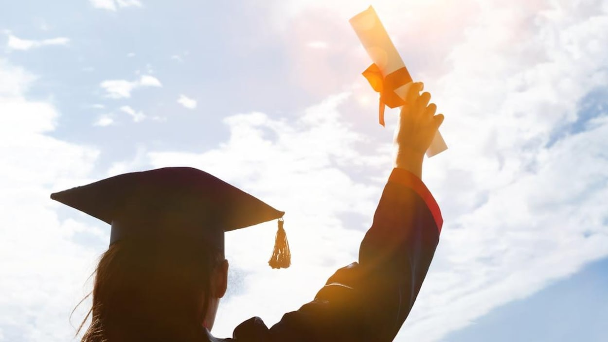 Un élève soulève son diplome lors de sa graduation.