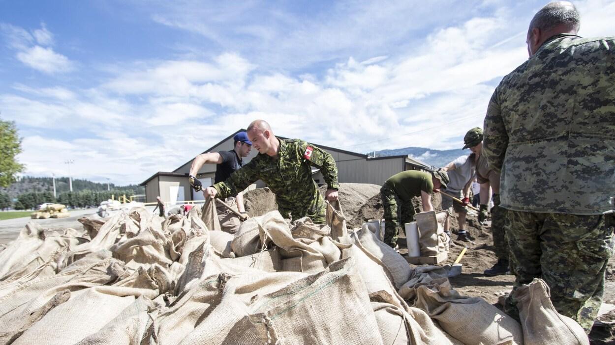 Des militaires remplissent des sacs de sable pour protéger la ville de Grand Forks en Colombie-Britannique, dont le centre-ville est inondé depuis une semaine.