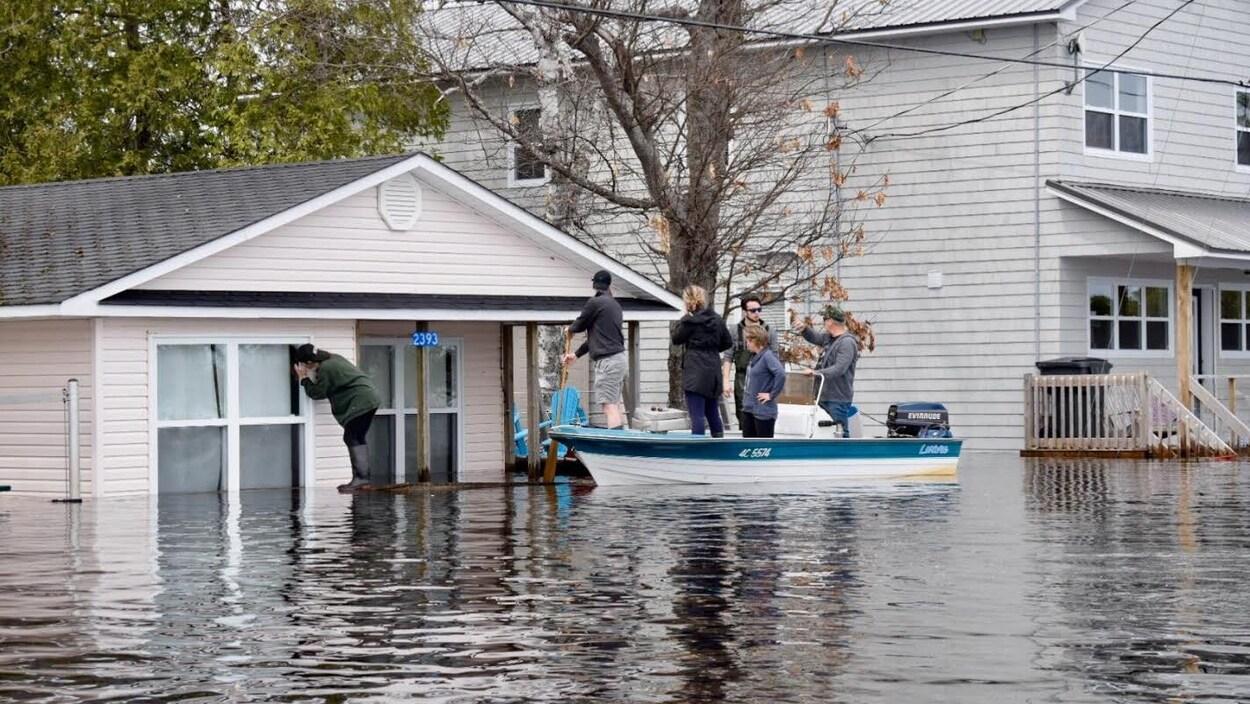 Des gens sur un canot près d'une maison inondée vérifient s'il y a toujours quelqu'un à l'intérieur.