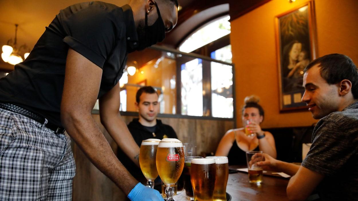 Un homme portant un masque de protection et des gants sert de la bière à des clients.