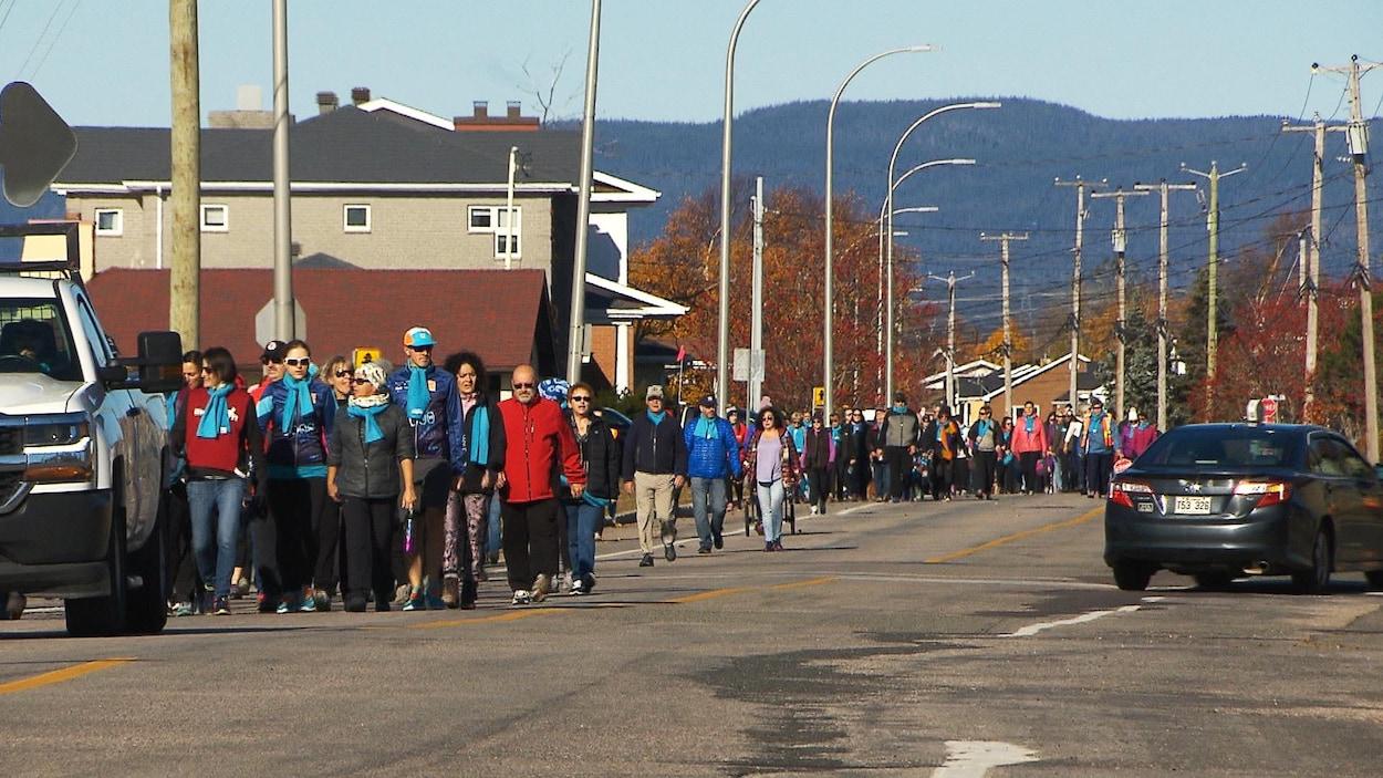 Un groupe de plusieurs dizaines de personnes marche dans la rue à Sept-Îles.