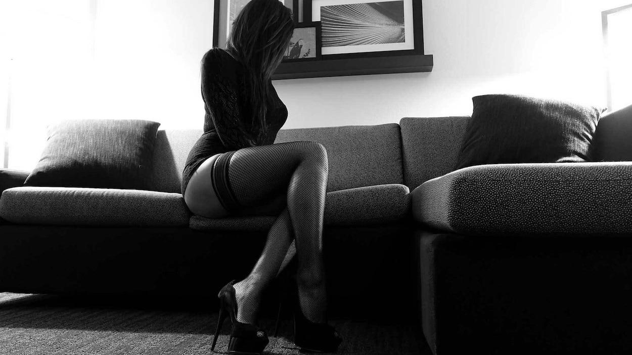 Photo d'une travailleuse du sexe dans une chamble d'hôtel.