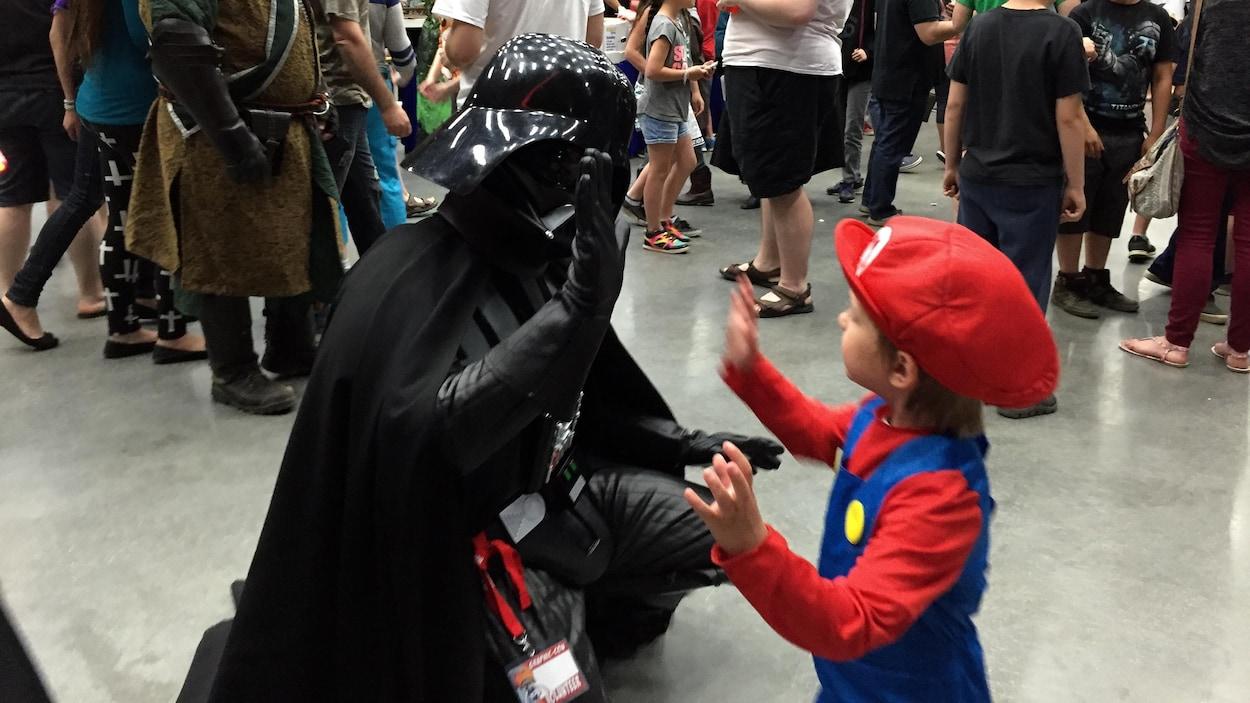 Un enfant déguisé en Mario Bros tape dans la main de Darth Vader