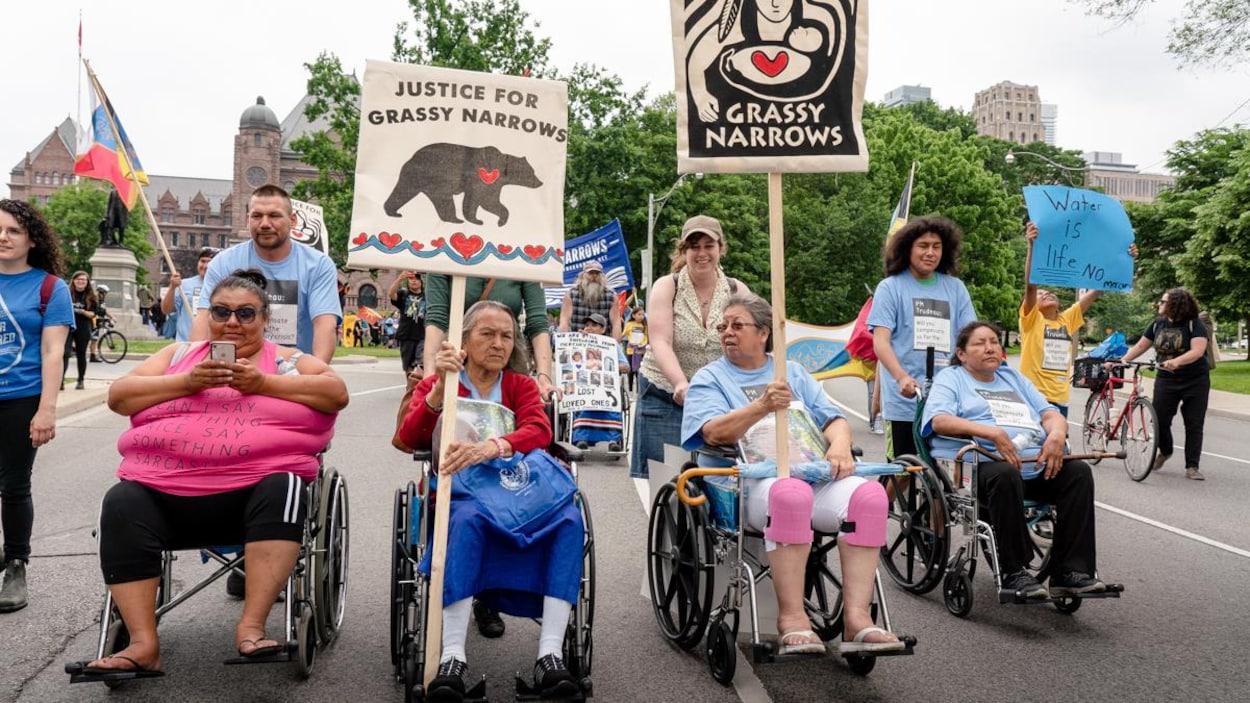 Des personnes âgées et handicapées portant des pancartes demandant justice pour la communauté autochtone.
