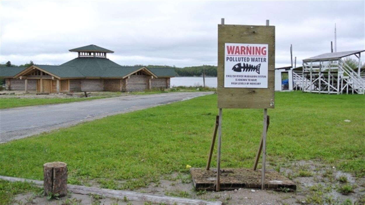 Un panneau d'avertissement indique que l'eau de la rivière est contaminée.