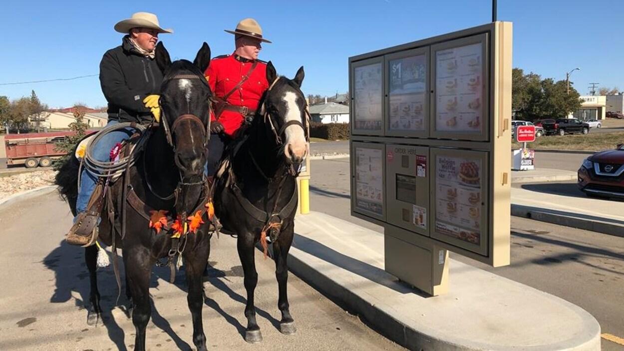 Deux hommes, chacun sur un cheval, en train de commander au service au volant d'un Tim Hortons en Saskatchewan.