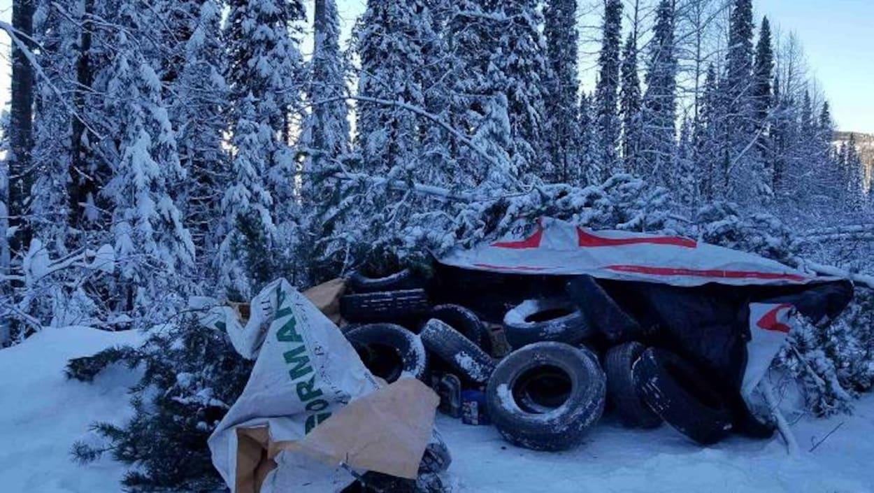 Des pneus sous une bâche, avec des arbres enneigés en arrière-plan.