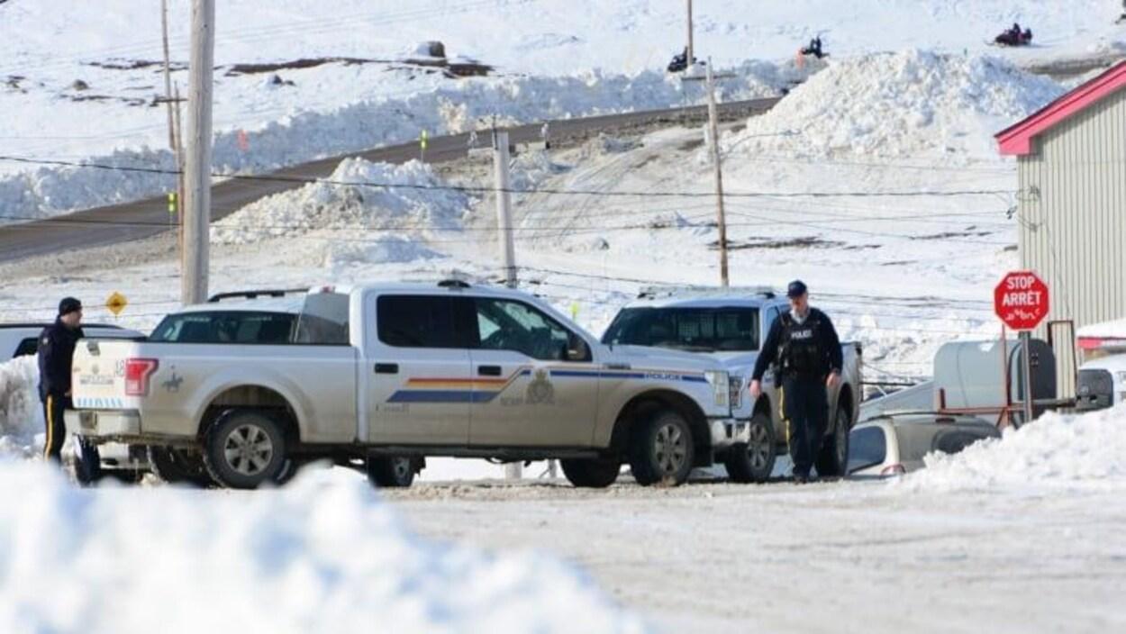 Des agents de la Gendarmerie royale du Canada devant des véhicules de police.