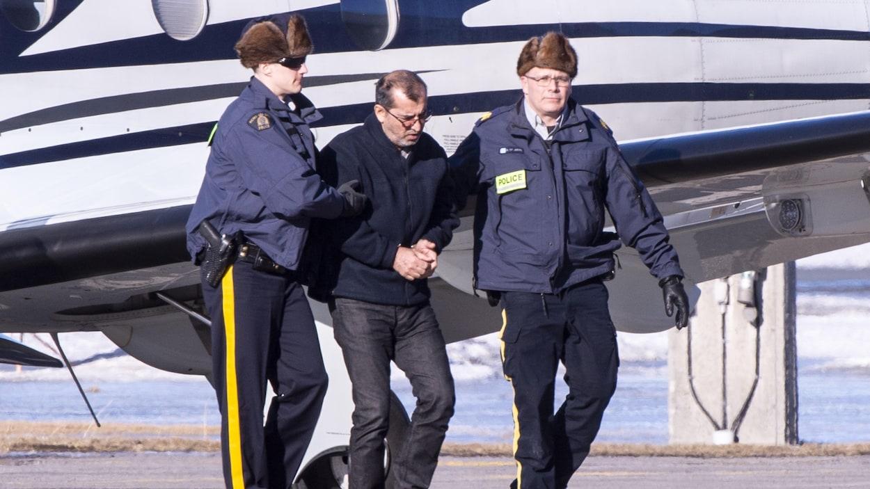 Des agents de la Gendarmerie royale du Canada escortent l'un des suspects arrêtés dans le cadre de l'opération Collecteur.