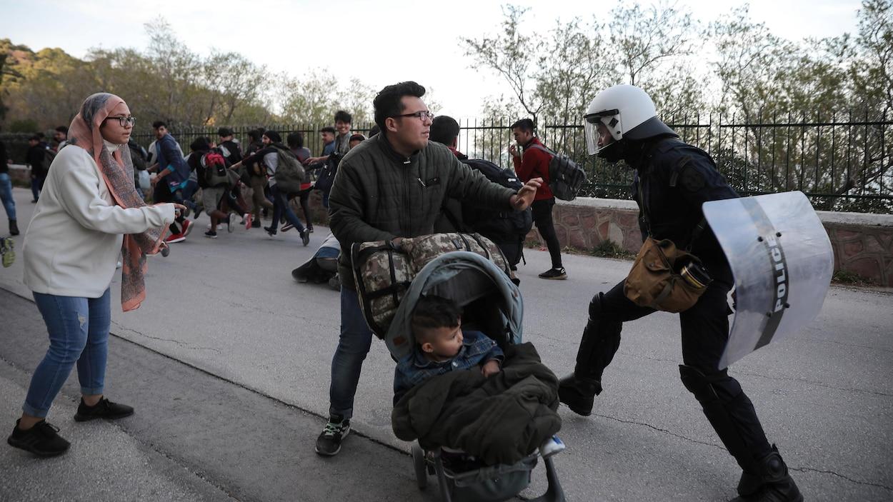Un policier frappe un homme tenant une poussette.