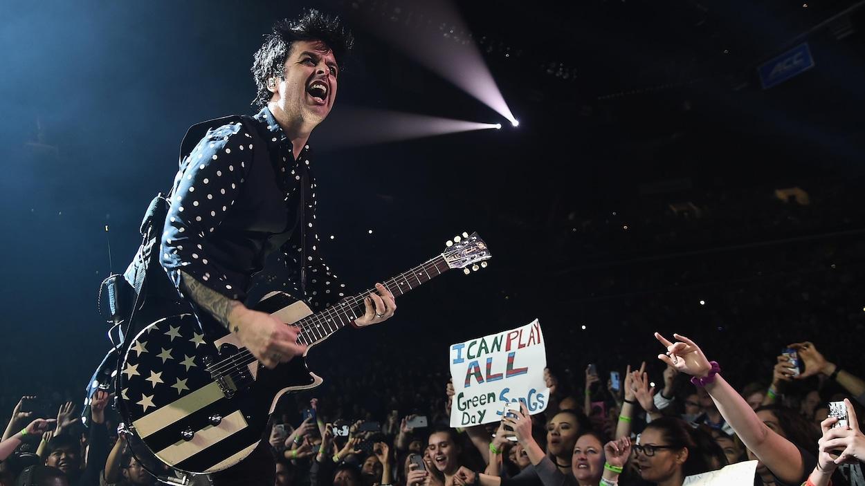 L'homme joue de la guitare et chante.