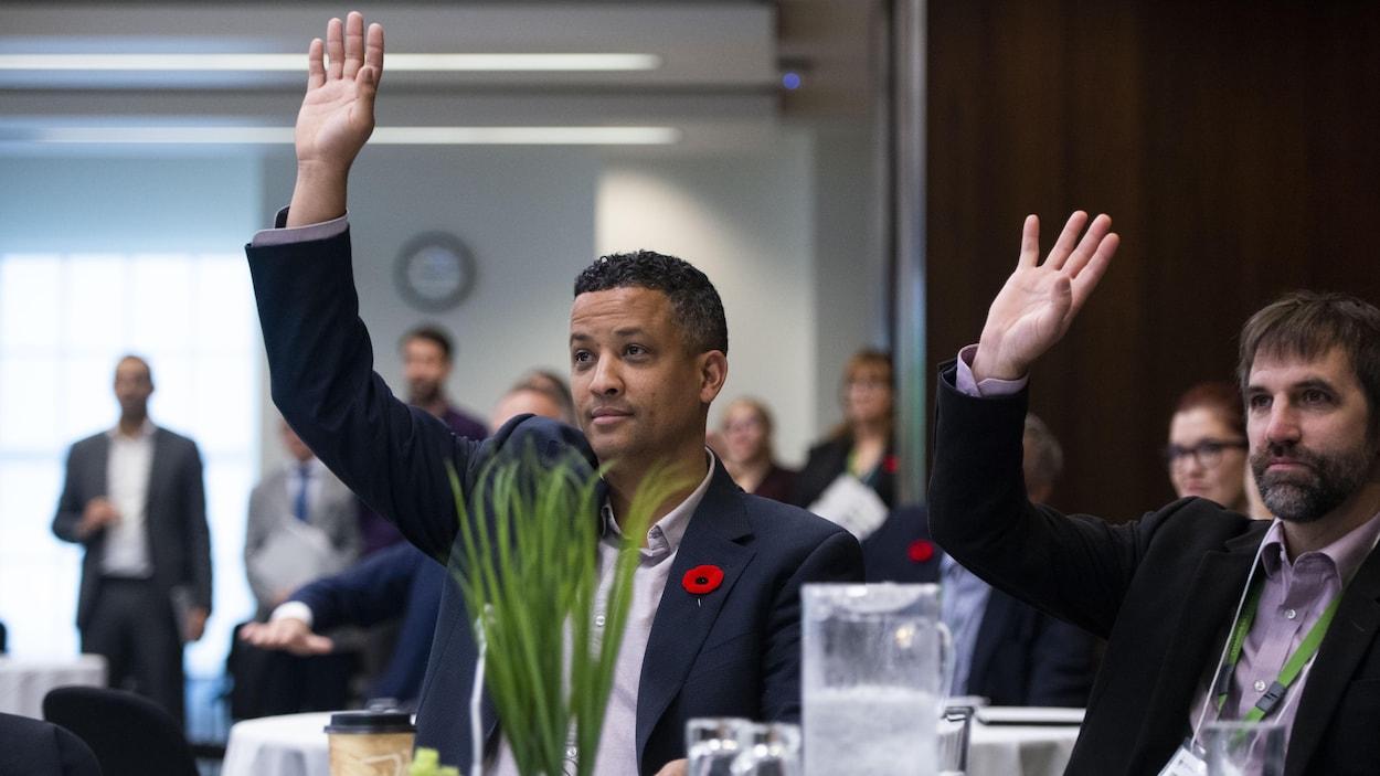 Deux hommes lèvent la main