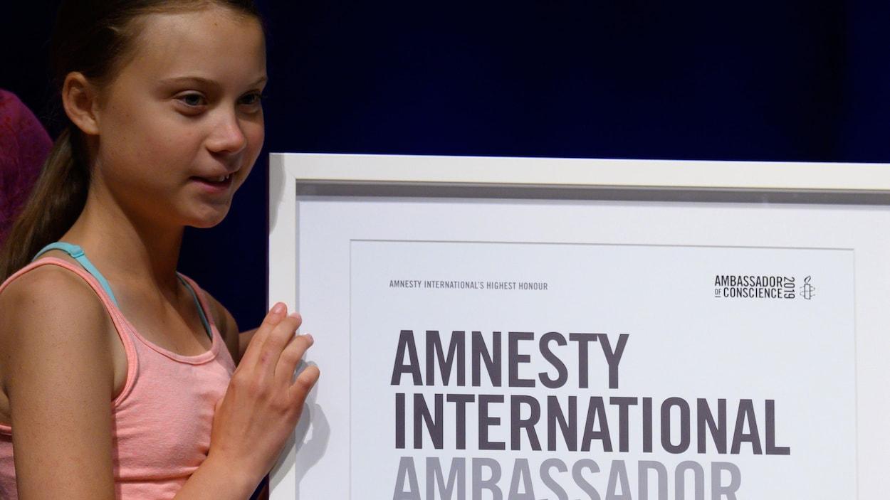 Greta Thunberg reçoit une plaque d'Amnistie Internationale.