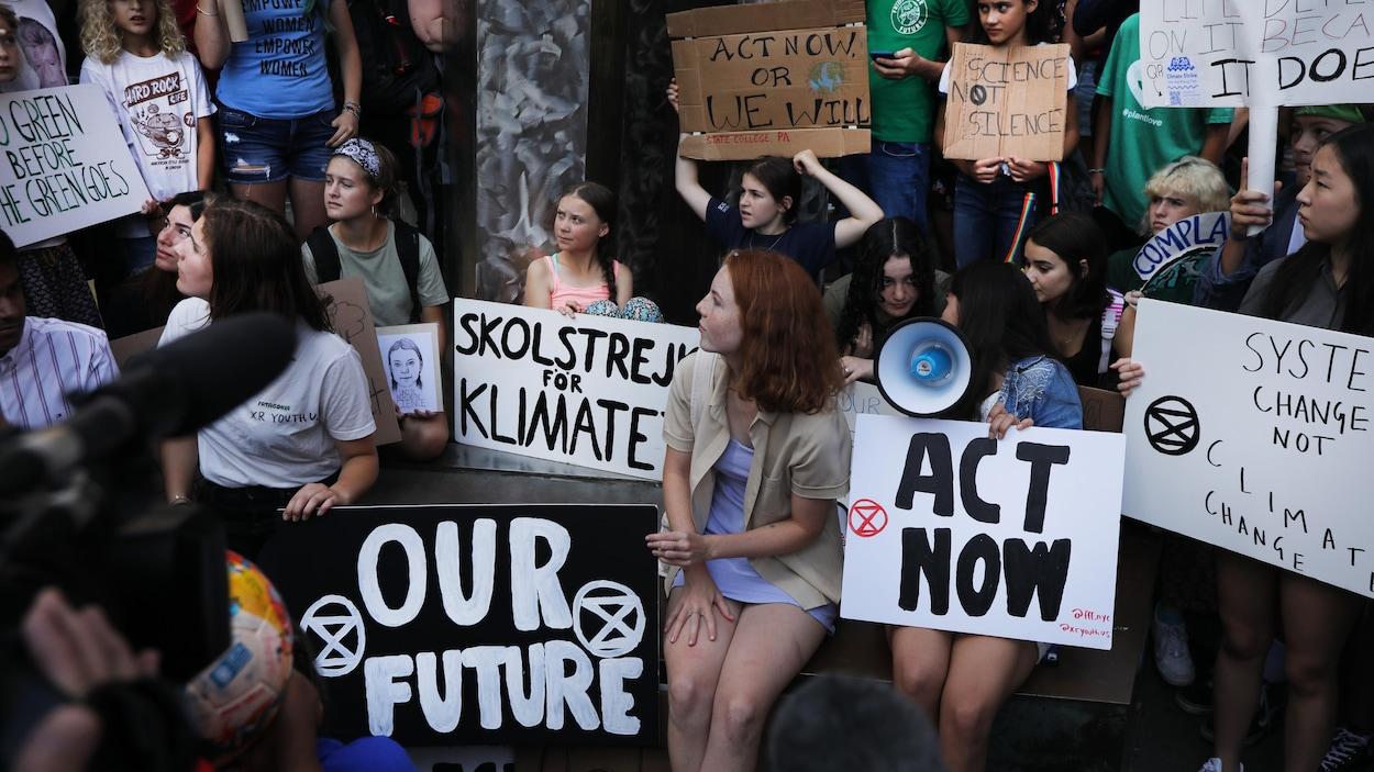 Des manifestants pour le climat sont assis avec des pancartes lors d'une manifestation à New York.
