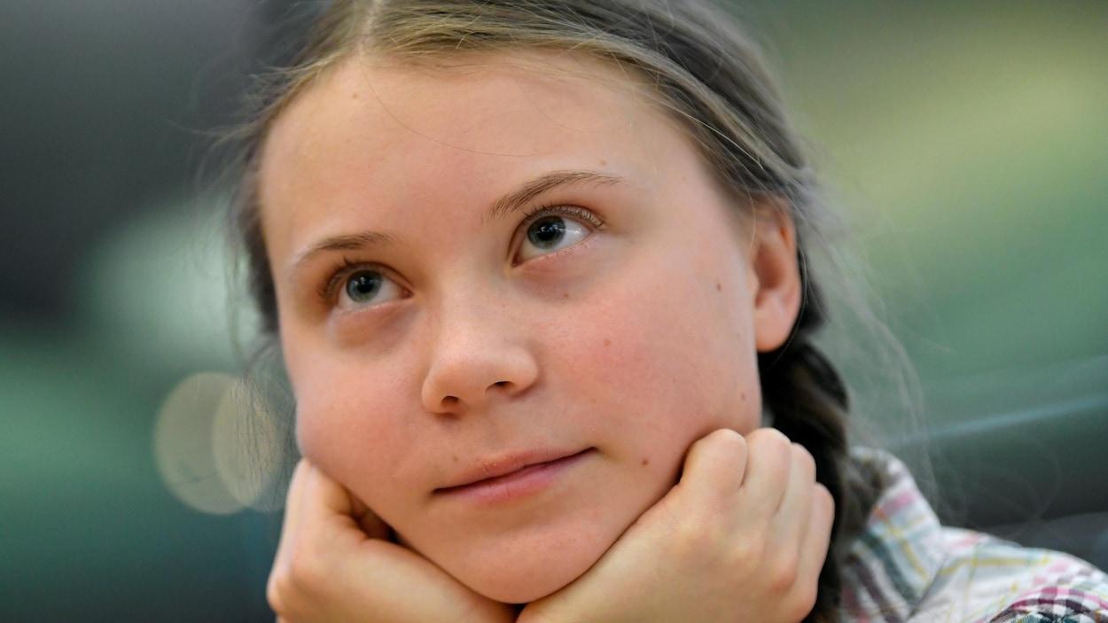 Greta Thunberg, vue de près, le visage entre les mains, regardant vers le haut.