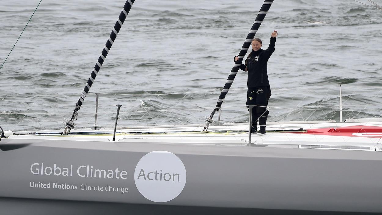 La jeune militante suédoise du climat Greta Thunberg, sur le voilier, salue les médias en levant la main droite.