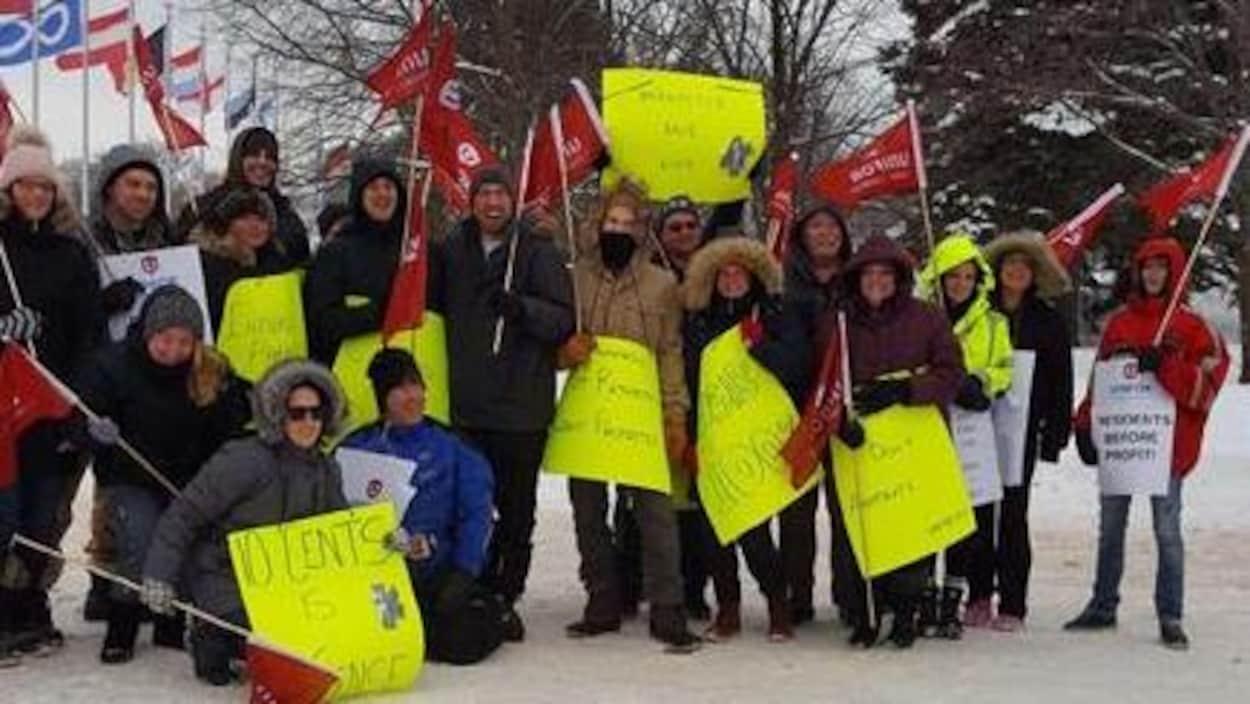 Des membres du syndicat Unifor avec drapeaux et pancartes à Sault-Sainte-Marie.