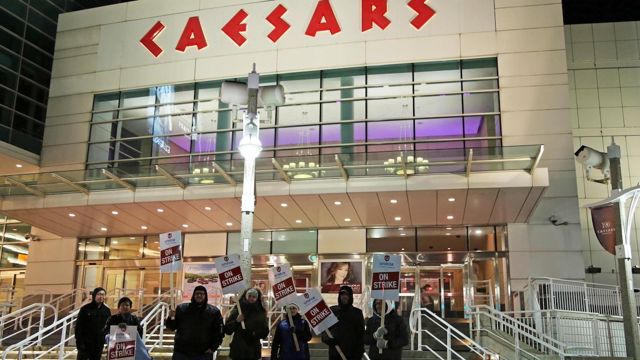 Des personnes tiennent des panneaux de grève devant l'entrée du casino